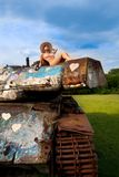 Junge Frau, die auf Armeebehälter aufwirft Stockfoto