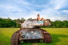 Junge Frau, die auf Armeebehälter aufwirft Stockbilder
