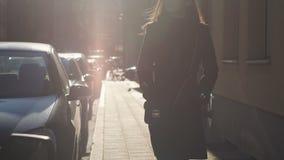 Junge Frau, die auf Bürgersteig unter Sonnenschein, Beginn des erfolgreichen Tages geht stock video