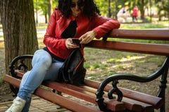 Junge Frau, die auf Bank in einem Park sitzt lizenzfreies stockbild