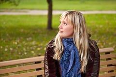 Junge Frau, die auf Bank am Herbstpark sitzt Lizenzfreie Stockbilder
