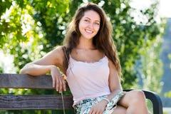 Junge Frau, die auf Bank sitzt Stockbild