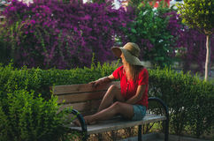Junge Frau, die auf Bank sitzt und beiseite, Alanya, die Türkei schaut Lizenzfreies Stockbild