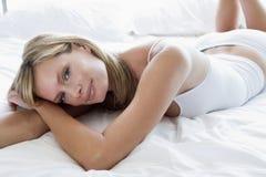 Junge Frau, die auf Bett legt Lizenzfreies Stockfoto