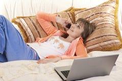 Junge Frau, die auf Bett mit Laptop liegt Stockfotos