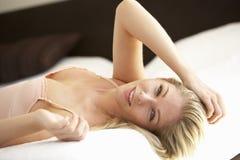 Junge Frau, die auf Bett sich entspannt Stockbild
