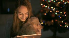 Junge Frau, die auf Boden sitzt und Tablette verwendet stock video footage