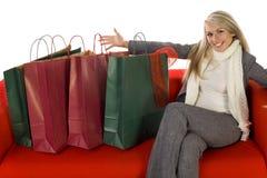 Junge Frau, die auf Couch mit Einkaufenbeuteln sitzt Stockfotos