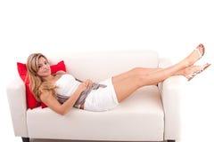 Junge Frau, die auf Couch sich entspannt Lizenzfreies Stockfoto