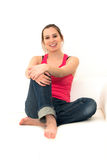 Junge Frau, die auf Couch sitzt lizenzfreie stockfotos