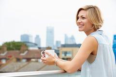 Junge Frau, die auf Dach-Terrasse mit Tasse Kaffee sich entspannt Stockfotografie