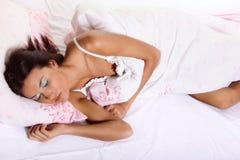 Junge Frau, die auf das Bett legt Lizenzfreie Stockbilder