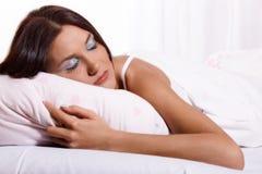 Junge Frau, die auf das Bett legt Stockbilder