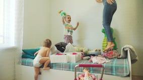 Junge Frau, die auf das Bett mit ihren Kindern springt stock video