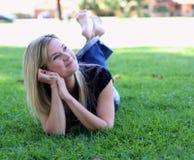 Junge Frau, die auf das Gras oben schaut legt Lizenzfreies Stockfoto