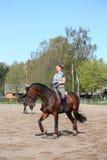 Junge Frau, die auf das Pferd trottet Stockfotos