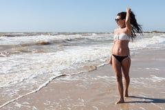 Junge Frau, die auf das Seeufer geht Stockfotos