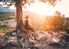 Junge Frau, die auf dem Berg bei Sonnenuntergang sitzt RAUM FÜR BEDECKUNGSschlagzeile UND TEXT stockfotografie