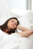 Junge Frau, die auf dem Bett schläft Stockfotografie