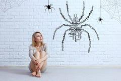 Junge Frau, die auf dem Boden sitzt und auf eingebildeter Spinne schaut stockfoto