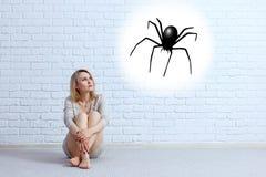 Junge Frau, die auf dem Boden sitzt und auf eingebildeter Spinne schaut stockbilder