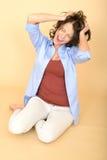 Junge Frau, die auf dem Boden trägt ein blaues Hemd und ein Weiß sitzt Stockbilder
