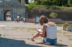Junge Frau, die auf dem Boden und dem Skizzieren sitzt Lizenzfreie Stockbilder
