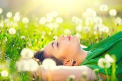 Junge Frau, die auf dem Feld im grünen Gras und im Löwenzahn liegt Lizenzfreie Stockfotografie