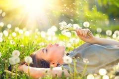 Junge Frau, die auf dem Feld im grünen Gras und in Schlaglöwenzahn liegt Lizenzfreie Stockfotografie