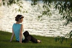 Junge Frau, die auf dem Flussufer stillsteht Stockbilder