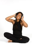 Junge Frau, die auf dem Fußboden hört Musik sitzt Stockfoto
