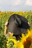 Junge Frau, die auf dem Gebiet mit Sonnenblumen geht Sch?nes junges M?dchen, das Natur auf dem Feld von Sonnenblumen bei Sonnenun stockbilder
