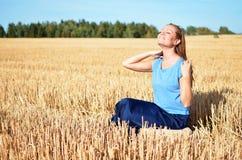 Junge Frau, die auf dem Gebiet sich entspannt Stockbild