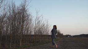 Junge Frau, die auf dem Gebiet während eines goldenen Stundensonnenuntergangs am Abend mit klarem blauem Himmel im Hintergrund wa stock video