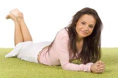 Junge Frau, die auf dem grünen Teppich liegt Stockfotos