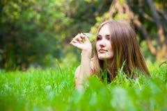 Junge Frau, die auf dem Gras liegt Lizenzfreie Stockfotos