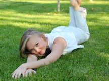 Junge Frau, die auf dem Gras liegt Stockfotos