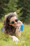 Junge Frau, die auf dem Gras liegt Stockbilder