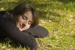 Junge Frau, die auf dem Gras sich entspannt Lizenzfreies Stockfoto