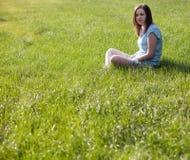Junge Frau, die auf dem Gras sitzt Lizenzfreies Stockbild