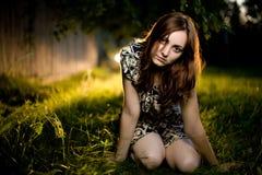 Junge Frau, die auf dem Gras sitzt Lizenzfreie Stockfotos