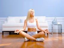 Junge Frau, die auf dem hölzernen meditierenden Fußboden sitzt Lizenzfreie Stockfotos