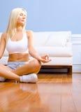 Junge Frau, die auf dem hölzernen meditierenden Fußboden sitzt Stockfotografie