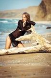 Junge Frau, die auf dem LOGON den Strand sitzt Lizenzfreies Stockbild