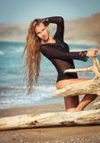 Junge Frau, die auf dem LOGON den Strand sitzt Stockbilder