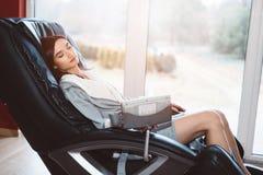 Junge Frau, die auf dem massierenden Stuhl sich entspannt stockfoto