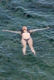 Junge Frau, die auf dem Meer sich entspannt Stockfoto