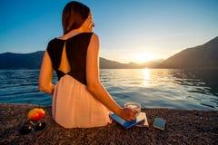 Junge Frau, die auf dem Pier bei Sonnenaufgang sitzt Stockbilder