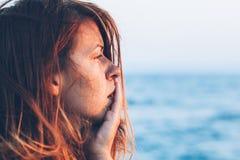 Junge Frau, die auf dem Pier traurig sich fühlt Stockfotos