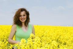 Junge Frau, die auf dem Rapsblumengebiet lacht Lizenzfreie Stockfotografie